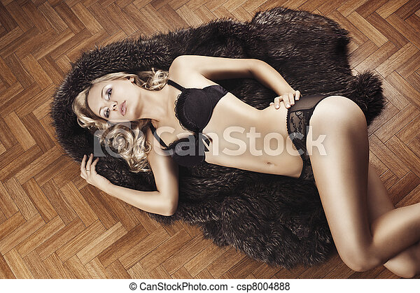 very beautiful blond and sexy young woman in underwear laying down on floor and covering with fur, she looks in to the lens with actractive eyes and touch left hip with left hand. - csp8004888