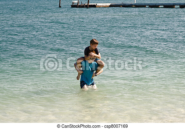 brothers are jumping and playing on a idyllic beach and having fun in the water