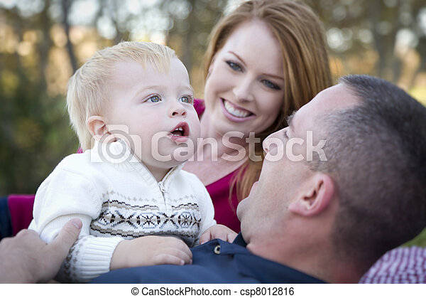 Cute Child Looks Up to Sky as Young Parents Smile - csp8012816