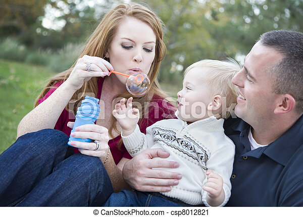 Young Parents Blowing Bubbles with their Child Boy in Park - csp8012821
