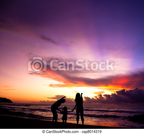 The silhouette of  family watching the sunrise on the beach - csp8014319