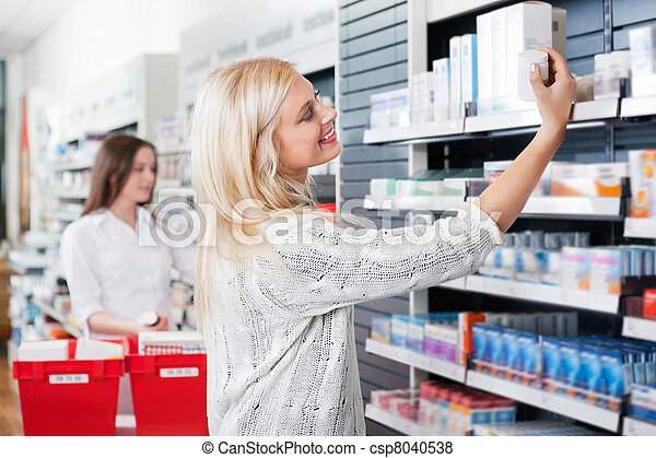 Woman Buying Medicine in Pharmacy - csp8040538