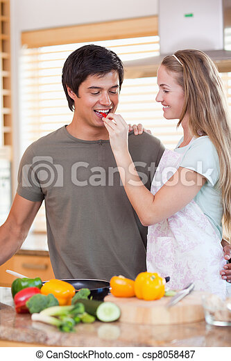 Portrait of a woman making her fiance tasting her meal - csp8058487