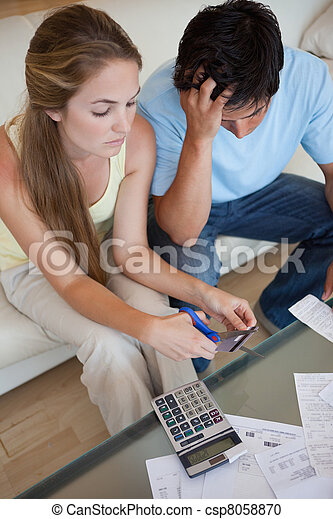 Portrait of a couple cutting their credit card - csp8058870