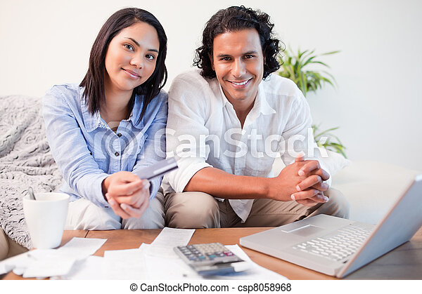 Couple doing online banking in the living room - csp8058968