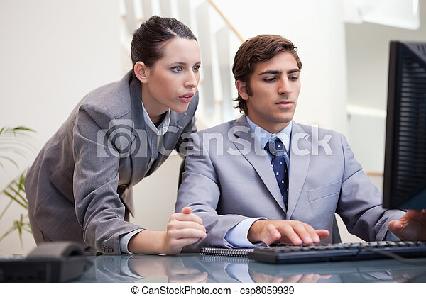 Business team looking at computer screen together - csp8059939