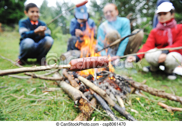 Barbecue in nature, group of people preparing sausages on fire (note: shallow dof) - csp8061470