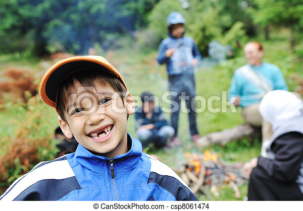 Barbecue in nature, group of children  preparing sausages on fire - csp8061474