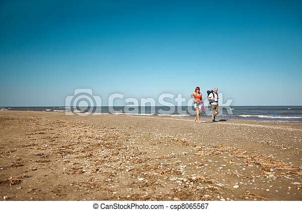 couple with backpacks walking on sea shore - csp8065567