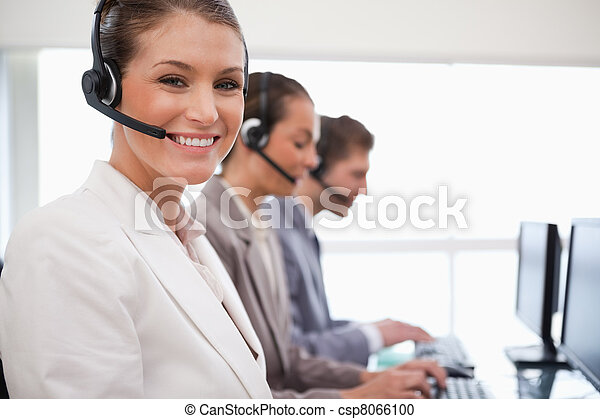 Smiling call center agent colleagues behind her - csp8066100