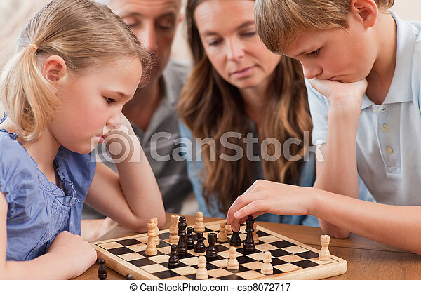 Close up of serious children playing chess in front of their parents in a living room - csp8072717