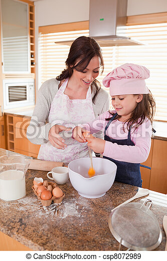 Portrait of a mother and her happy daughter baking - csp8072989