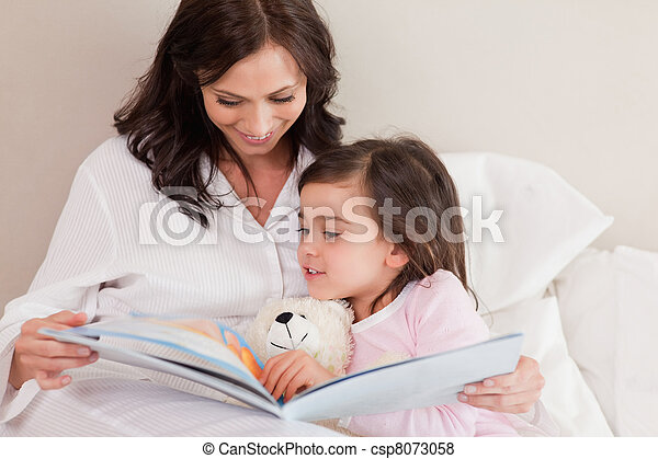 Mother reading a story to her daughter - csp8073058