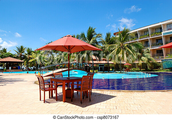 The table and chairs of outdoor restaurant near  swimming pool at luxury hotel, Bentota, Sri Lanka - csp8073167