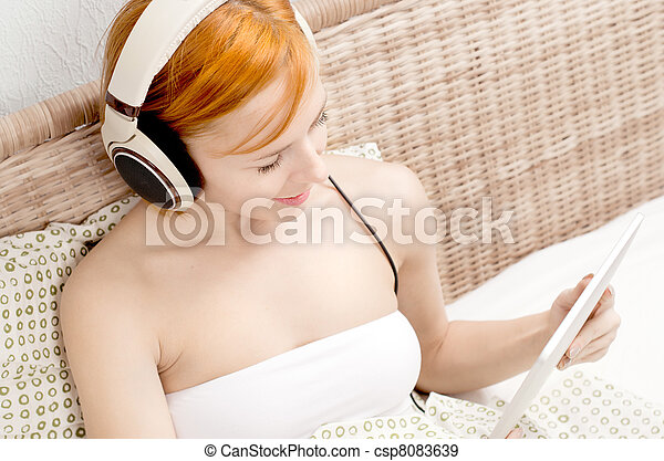 Red woman in bed listening to the music - csp8083639