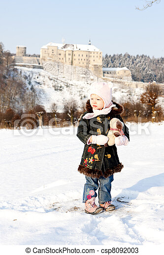 standing little girl and Cesky Sternberk Castle in winter at background, Czech Republic - csp8092003