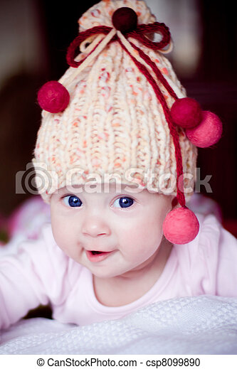 cute baby girl in yellow hat with colourfu bobbles - csp8099890