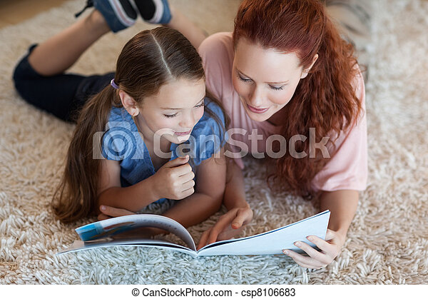 Mother and daughter on the carpet reading - csp8106683