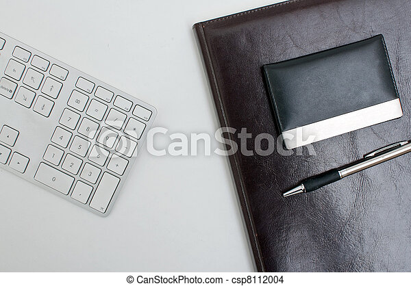 Stock Photo of Office desk detail, a computer keyboard, agenda and a pen on...