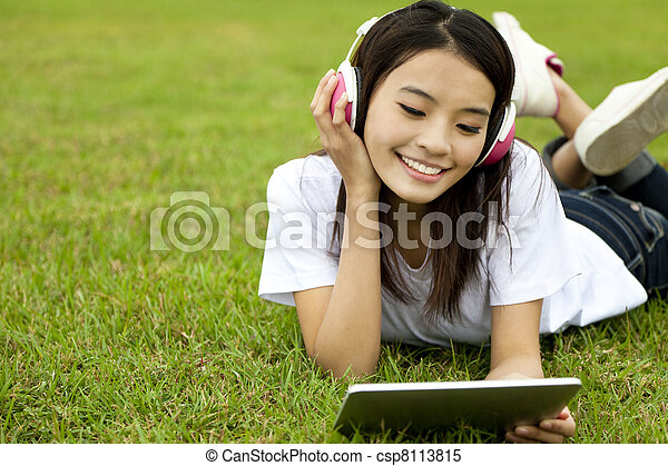 happy girl using tablet pc on the grass - csp8113815