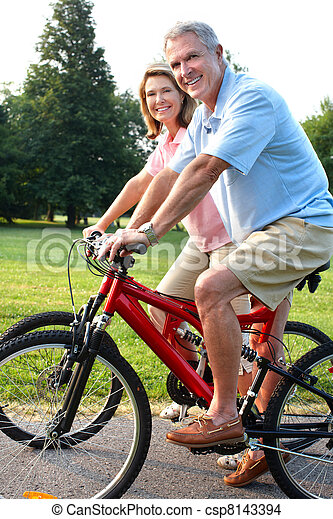 Senior couple cycling in park. - csp8143394