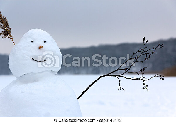 Snowman Waving its Twig Arm in Greeting before a Frozen Lake - csp8143473