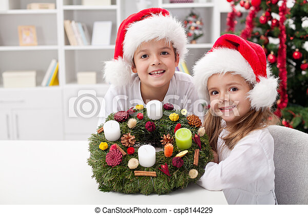 Kids with self decorated advent wreath - csp8144229