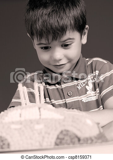 Boy blowing candles on cake, happy birthday party - csp8159371