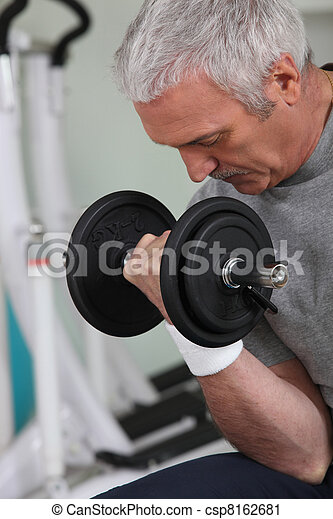 mature white-haired man lifting weight in sports room - csp8162681