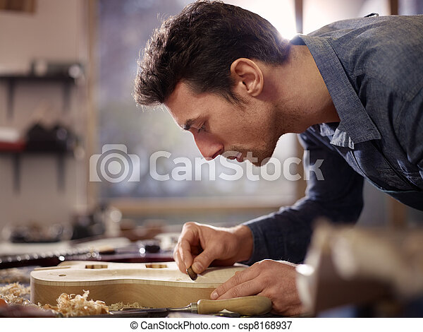 Italian artisan working in lutemaker workshop - csp8168937