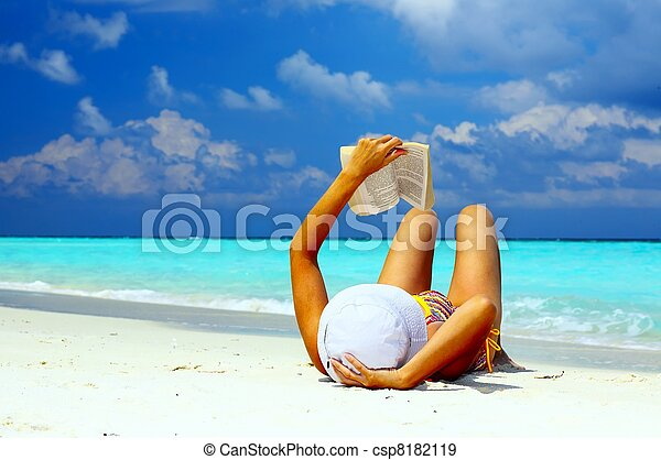 Young women is reading on the coral beach - csp8182119