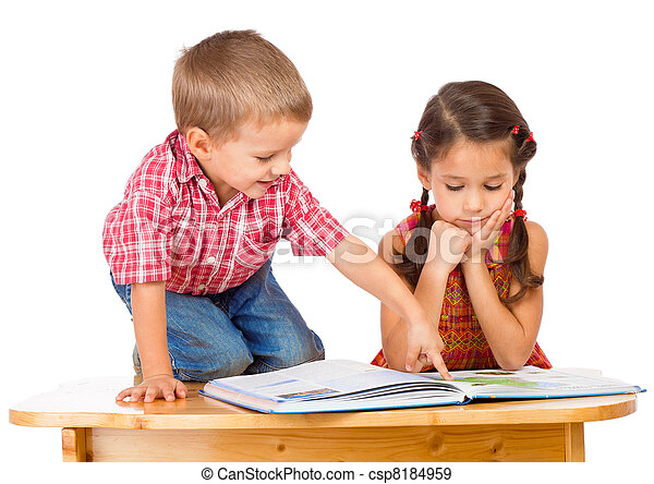 Two smiling children reading book on the desk - csp8184959