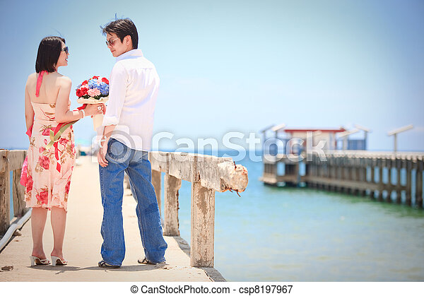 couples make eye contact at pier on the beach - csp8197967
