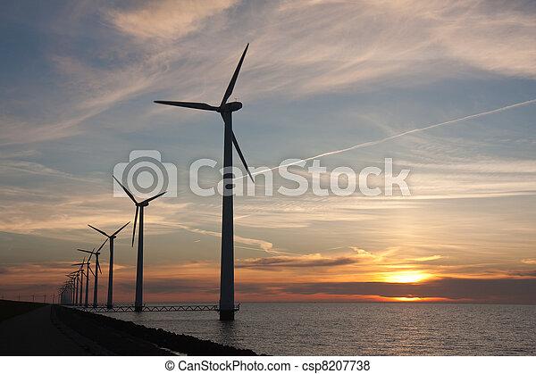 Dutch offshore windturbines during a beautiful sunset - csp8207738