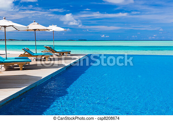 Deck chairs and infinity pool over tropical lagoon - csp8208674
