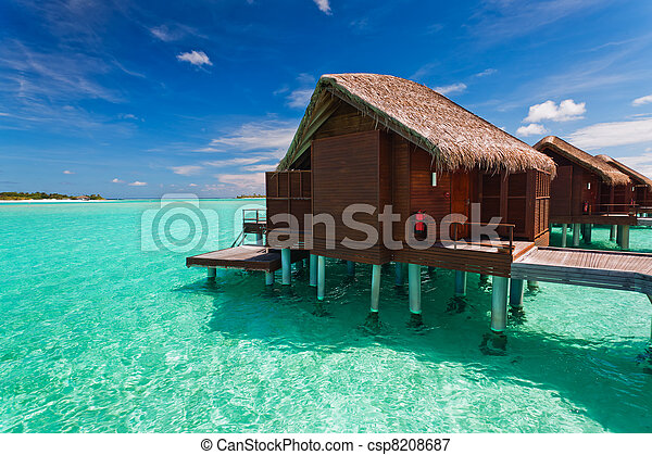 Over water bungalow with steps into tropical lagoon - csp8208687