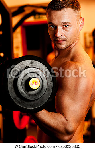 Man exercising his arm muscles by lifting two dumbell free weights in a fitness club. - csp8225385