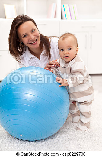 Little baby girl stands by a large exercise ball - csp8229706