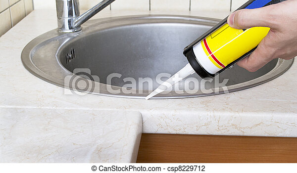 Plumber putting a silicone sealant to installing a kitchen sink - csp8229712