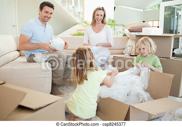 Family unpacking cardboard box in the living room - csp8245377