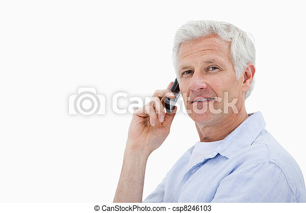 Side view of a man making a phone call while looking at the camera against a white background - csp8246103