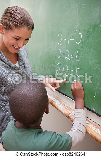 Portrait of a beautiful teacher and a pupil making an addition - csp8246264
