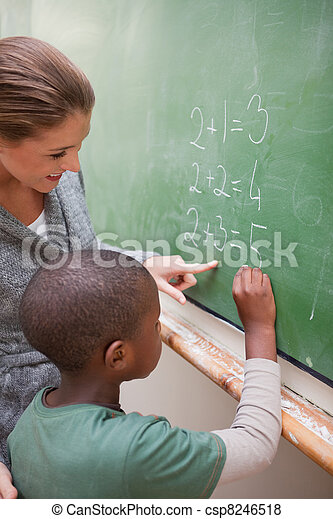 Portrait of a cute teacher and a pupil making an addition - csp8246518