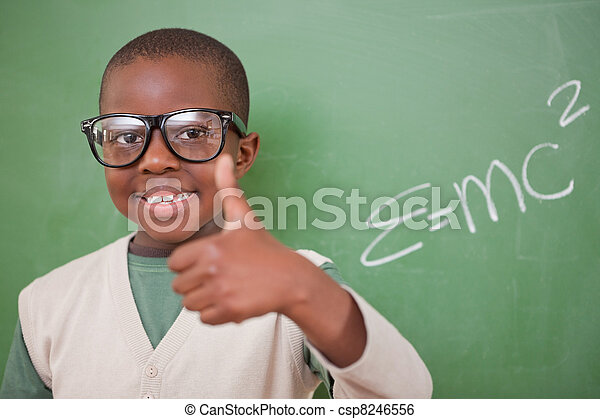 Schoolboy posing with the the mass-energy equivalence formula and the thumb up in front of a blackboard - csp8246556