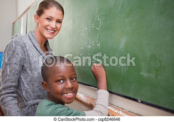 Smiling teacher and a pupil making an addition - csp8246646
