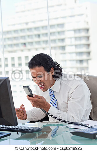 Portrait of a angry businessman shouting at his handset - csp8249925