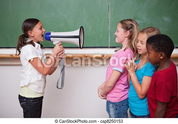 Schoolgirl yelling through a megaphone to her classmates - csp8250153