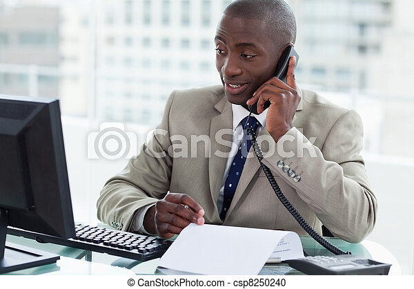 Smiling entrepreneur making a phone call while looking at his computer in his office - csp8250240