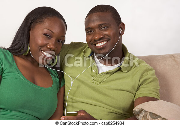 Happy young ethnic black couple listening music - csp8254934
