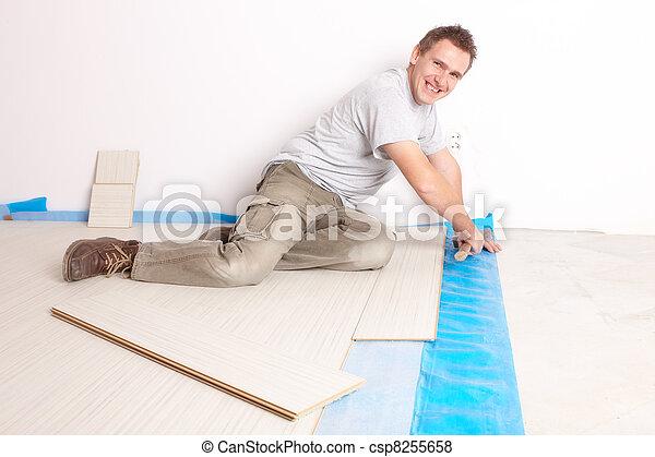 Worker installing a laminated flooring - csp8255658